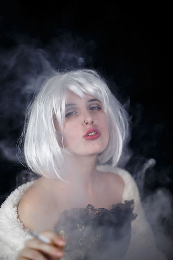 Portrait Of Female Model Smoking Cigarette Against Black Background