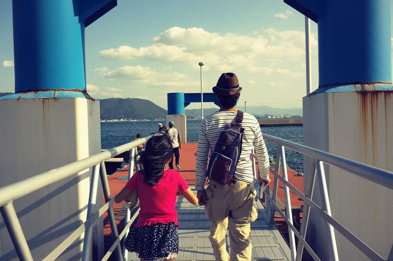 Rear View Of Father And Daughter Walking On Pier At Lake