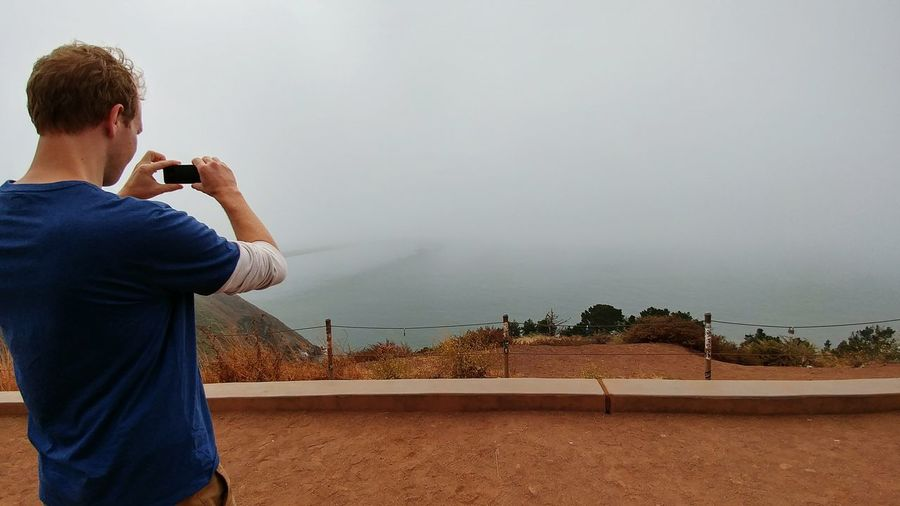 A man photographing the San Francisco bay fog as it rolls in, obscuring everything. Marin Headlands, CA. One Man Only Man Taking Photo Foggy Scene San Francisco Bay Area Marine Layer San Francisco Fog Marin Headlands Obscured Uncertainty  The Unknown EyeEm Selects One Person Adult Adults Only Standing