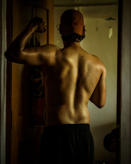 Rear view of shirtless man flexing muscles standing at home