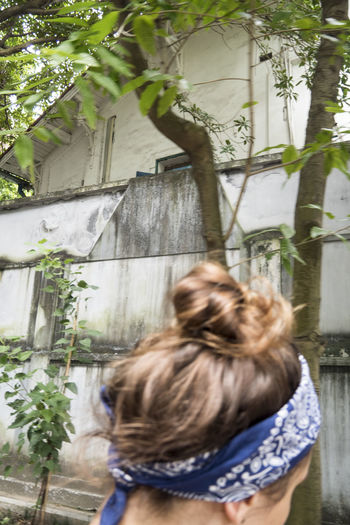 Rear view of woman in front of building
