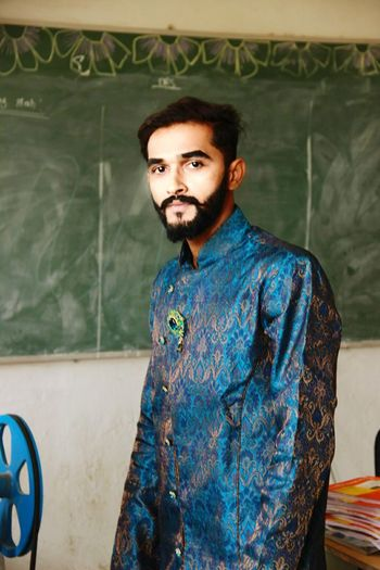 Portrait Of Young Man In Traditional Clothing Standing Against Green Board In Classroom
