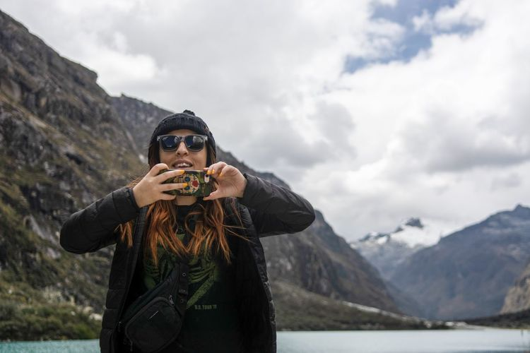 Portrait of woman wearing sunglasses holding mobile phone against mountains