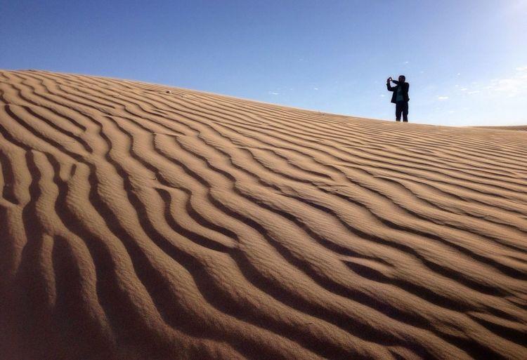 Man Photographing In Desert Against Sky