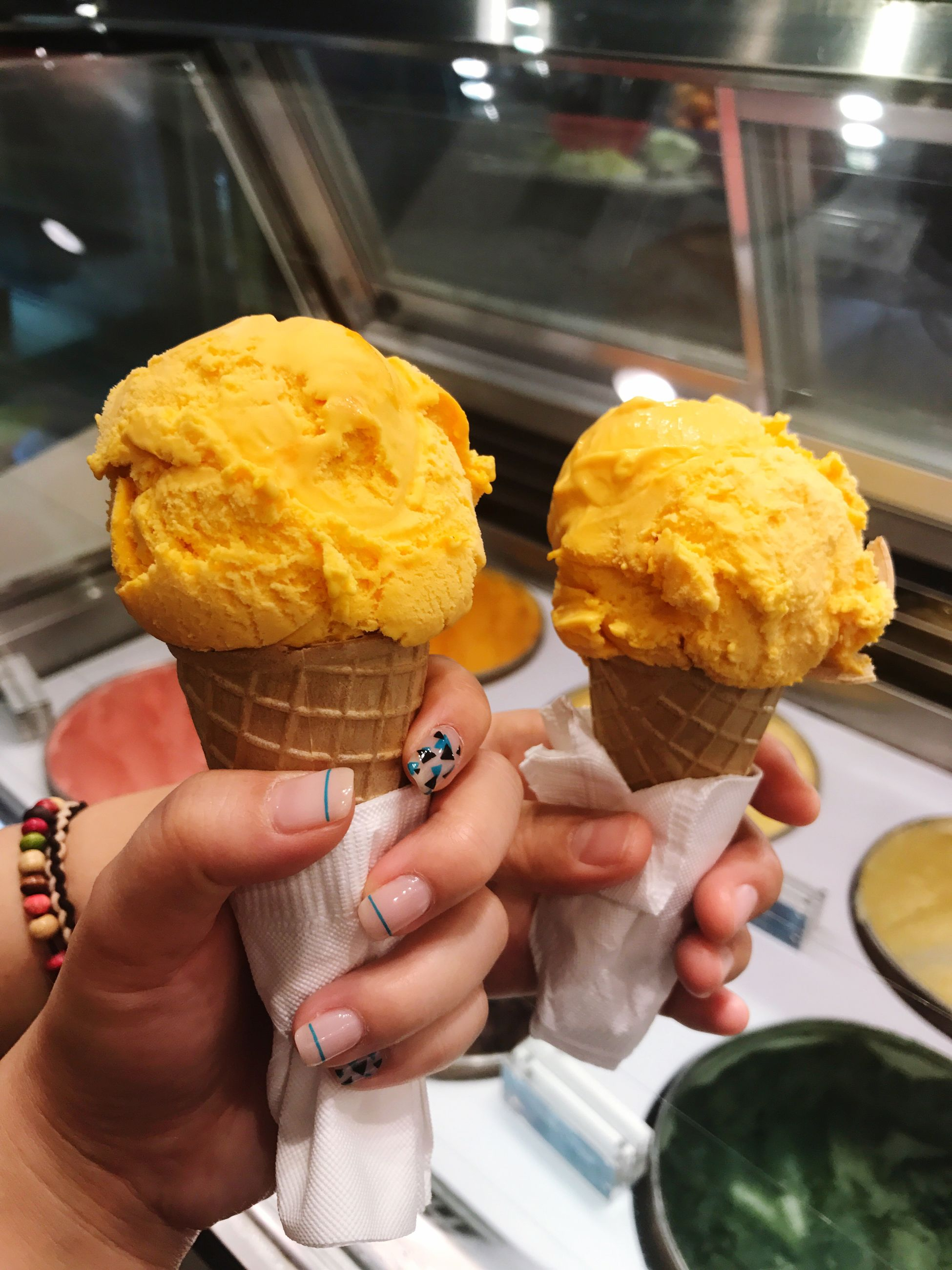 human hand, food and drink, frozen food, sweet food, ice cream, food, dessert, indulgence, human body part, unhealthy eating, holding, temptation, real people, ice cream cone, freshness, ready-to-eat, frozen sweet food, close-up, indoors, day, men, women, scoop shape, ice cream parlor, people