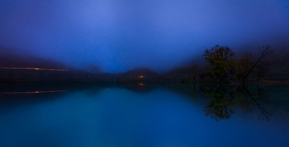 Scenic view of lake against blue sky at night