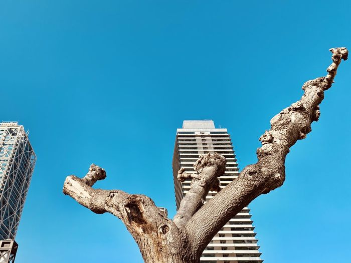 Low angle view of sculpture against clear blue sky