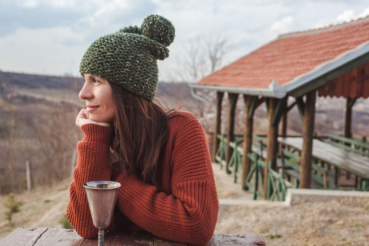 Smiling woman looking away with drink in container on table during winter