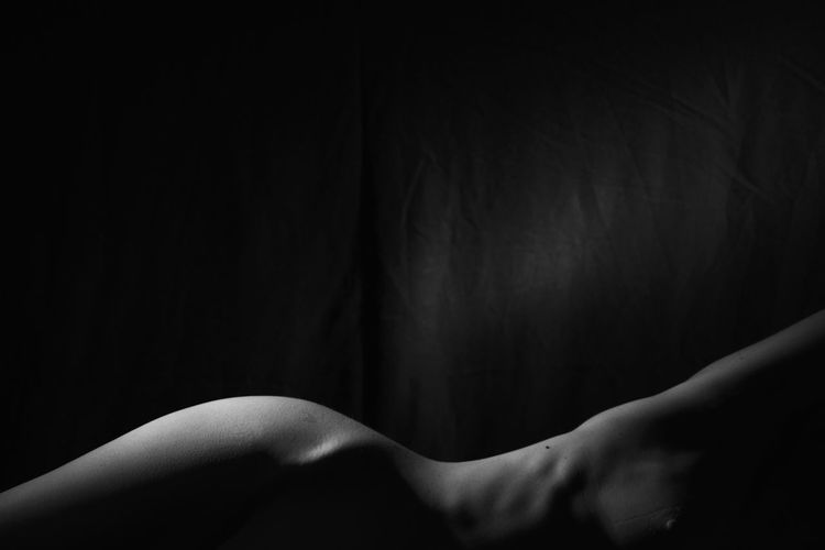 Midsection of naked woman lying against black background