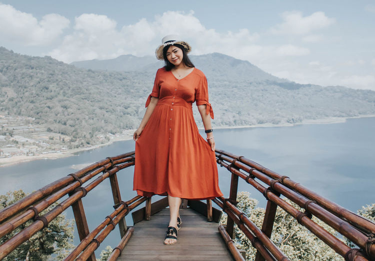 Portrait of woman standing on railing against mountain