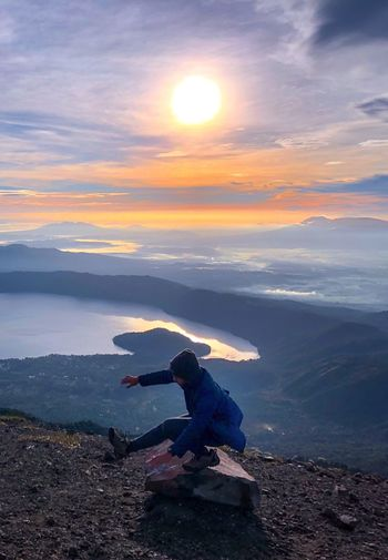 Man balancing on rock at mountain against sky during sunset