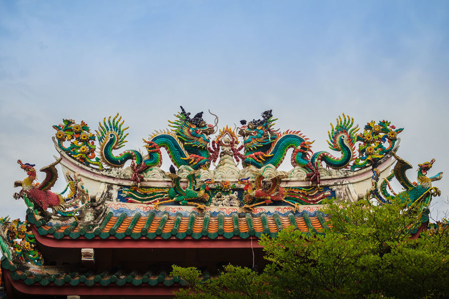 Beautiful two large grimace dragons crawling on decorative tiles roof in Chinese temple. Colorful roof detail of traditional Chinese temple with two dragon on blue sky background. Blue Sky White Clouds Chinese Temple Ancient Architecture Dragon Dragon Sculpture Dragons Animal Representation Architecture Art And Craft Belief Blue Dragon Blue Sky Blue Sky And White Clouds Blue Sky Background Blue Sky With Clouds Building Exterior Built Structure Chinese Culture Chinese Dragon Chinese Temple Chinese Temple Decoration Chinese Temples Crawling Creativity Day Decorative Tile Decorative Tile Art Decorative Tiles Dragon Scales Dragon Statue Dragon Statues Dragon Stone Grimace Low Angle View Multi Colored Nature No People Ornate Outdoors Place Of Worship Religion Representation Sculpture Sky Spirituality Statue Tiles Roof