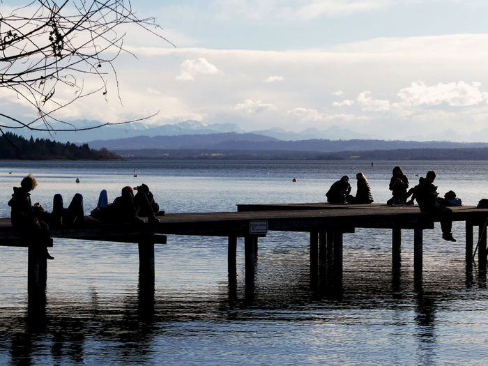 Silhouette people sitting on pier in lake against cloudy sky