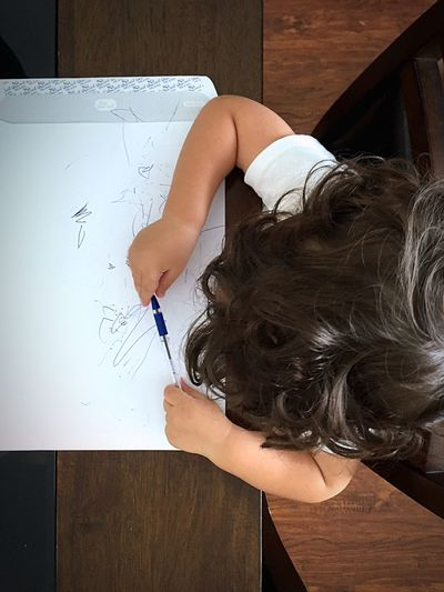 Overhead View Of Baby Scribbling On Paper At Table