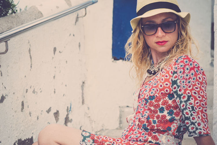 Portrait of woman wearing sunglasses sitting against wall
