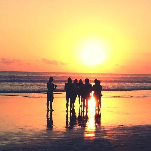 Silhouette People Standing At Beach Against Orange Sky