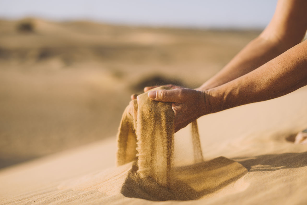 Close-up of hands with sand