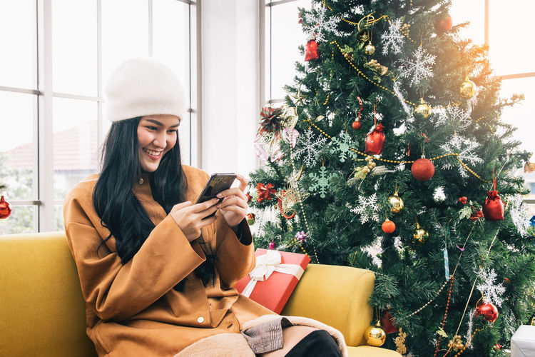Young woman using mobile phone while sitting on sofa by christmas tree