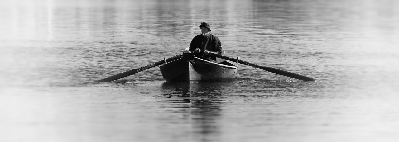 Rear view of man on boat in water