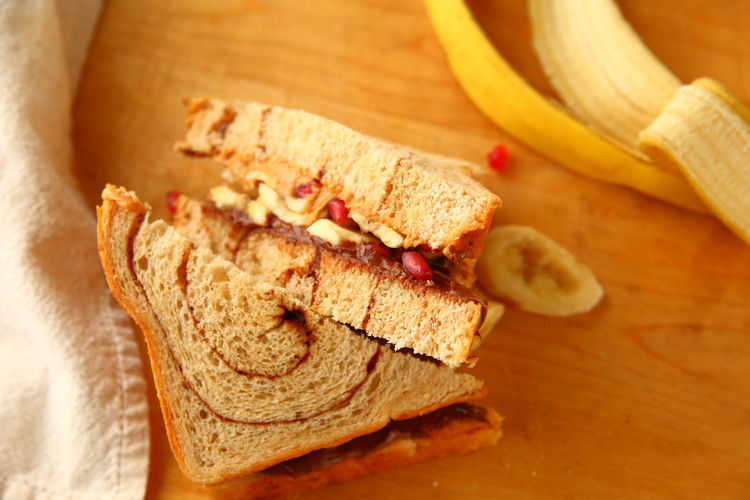 Peanut butter, banana and chocolate spread sandwich Breakfast Homemade Food Lunch Natural Light Textures Bananas Breakfast Cinnamon Swirl Bread Close-up Cutting Board Delicious Fabric Food Preparation Indoors  Light Meal Napkin No People Overhead Peanut Butter Sandwich Pomegranate Seeds Snack Sweet Food Tasty Wood - Material
