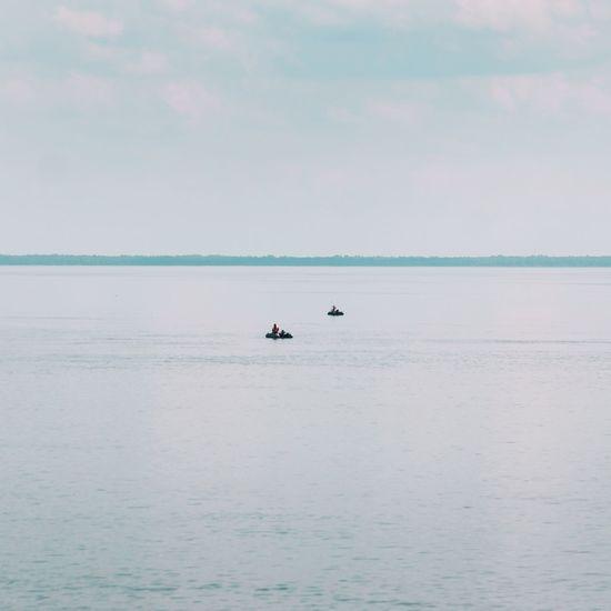 People traveling on sea against sky