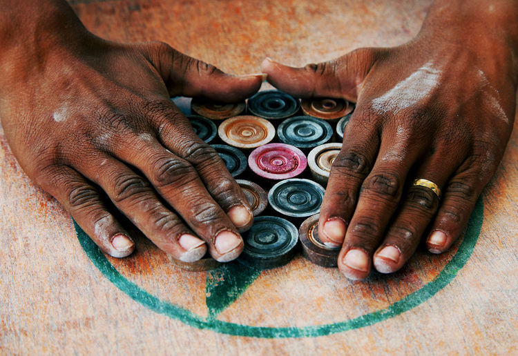 Cropped hands arranging carrom men