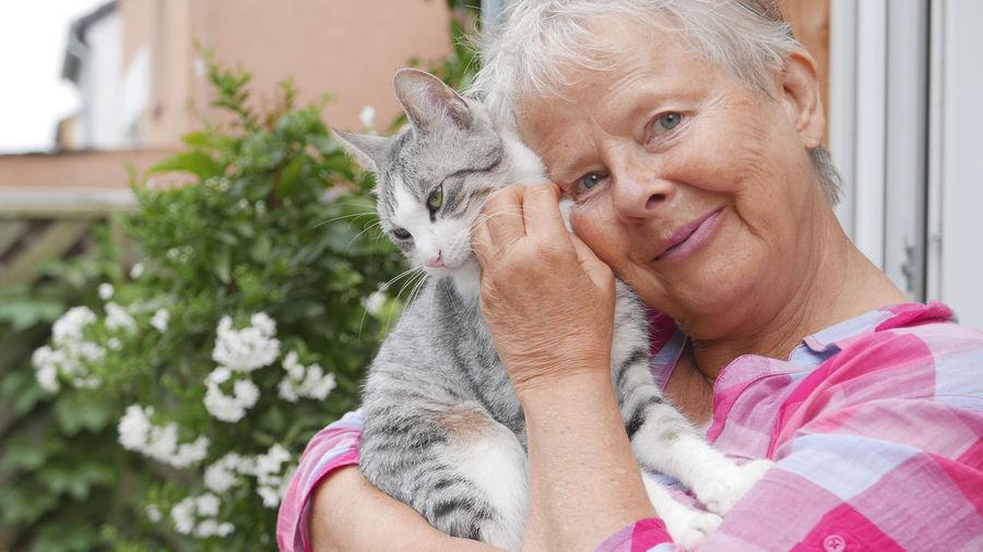 Portrait of senior woman cuddling tabby cat by house