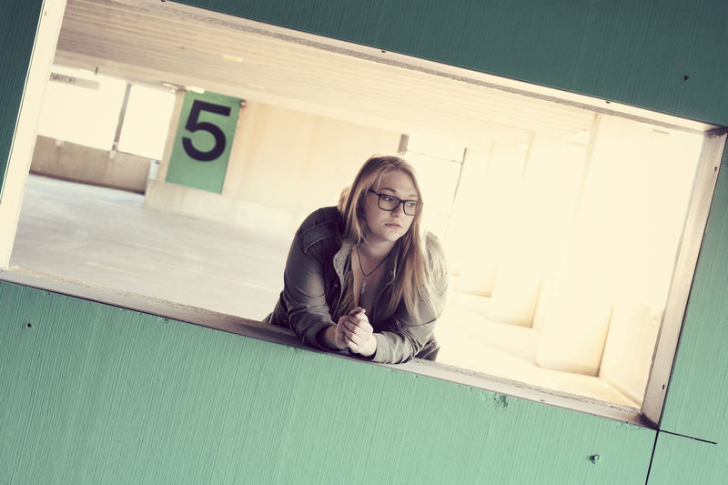 Young woman leaning on railing at parking lot