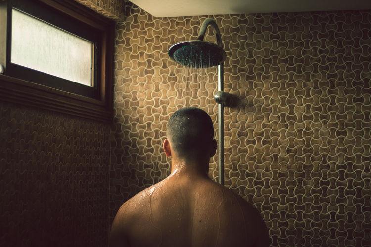 Rear view of shirtless man taking shower against wall at home