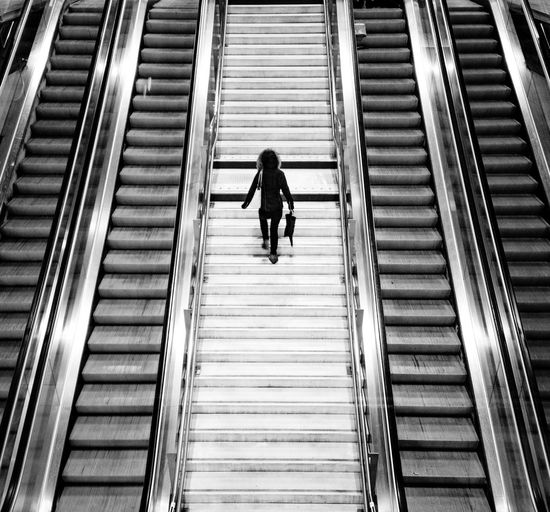 Rear view of woman walking on escalator