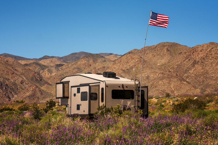 Caravan parked in Joshua Tree national park Mountain Beauty In Nature Nature Environment Mountain Range No People Day Patriotism Flag Scenics - Nature Landscape Sunlight Tranquil Scene Flower Clear Sky Motorhome Camping Freedom America American Flag Caravan Outdoors Joshua Tree National Park California