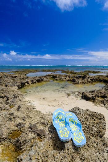Flip-flop on rocky sea shore against sky