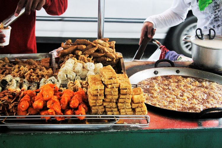 Midsection Of People Having Food At Stall