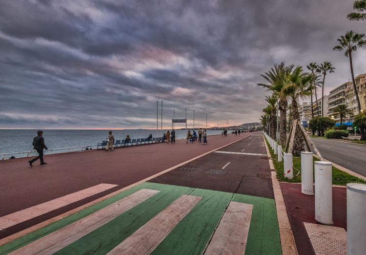 People on footpath by sea against sky