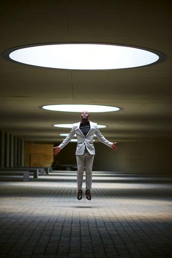 Full length of man standing against illuminated lights