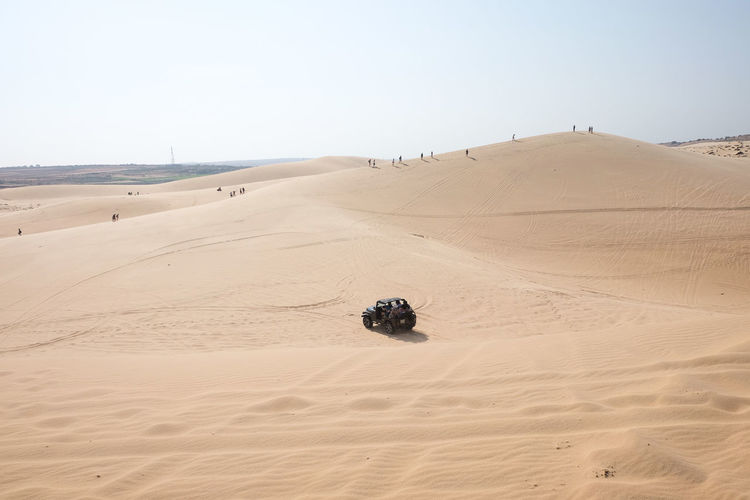 Off-Road Vehicle On Sand At Desert Against Clear Sky