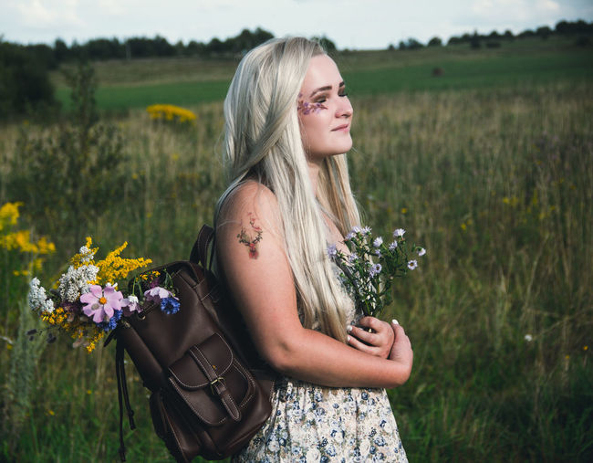 Beautiful young woman standing by flower field
