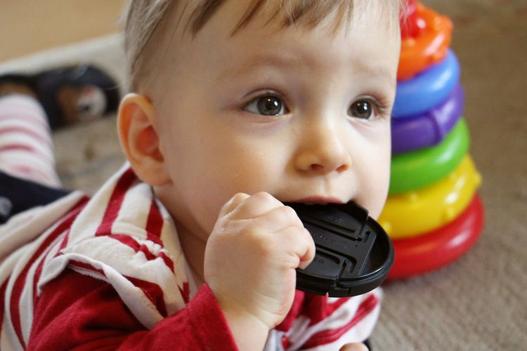 Close-up of baby with camera lens cover in mouth