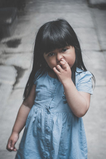 Portrait Of Girl Picking Nose While Standing On Footpath