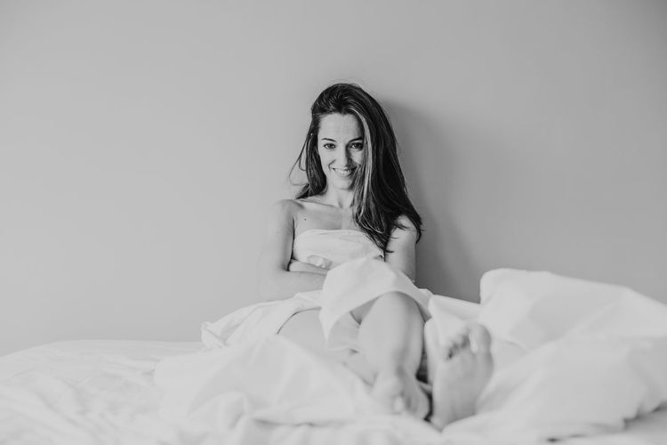 Portrait of smiling woman with blanket sitting on bed against wall