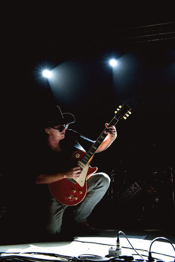 Low angle view of man playing guitar at night