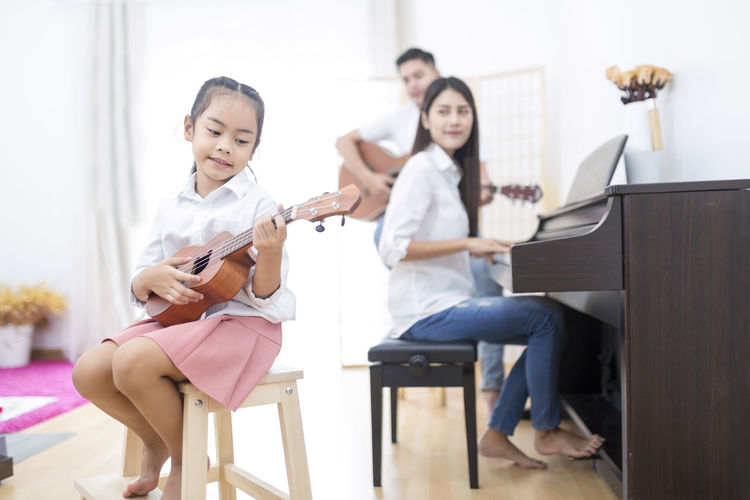 Asian family,daughter playing ukulele,father playing guitar,mother playing piano in family band at home, concept for family relationship Asian  Family Happy Home Learning Love Mother Music Piano Relationship Childhood Daughter Education Entertainment Father Girls Guitar Indoors  Media Musical Instrument Musician Playing Song Together Ukulele