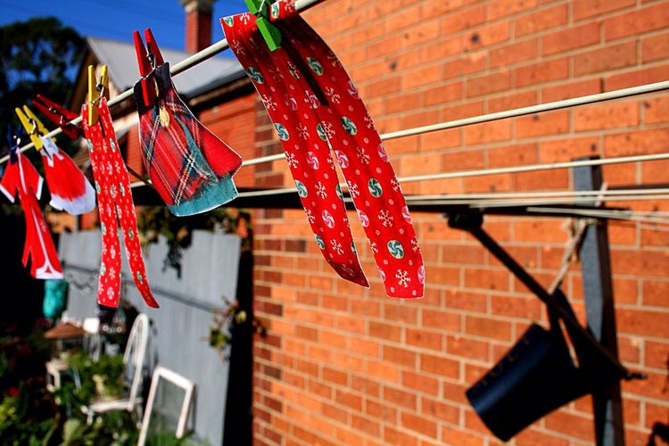 Christmas Decorations Hanging On Clothesline Against Brick Wall
