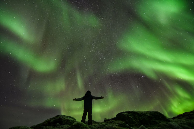 Low angle view of silhouette mature man with arms outstretched standing against northern lights at night