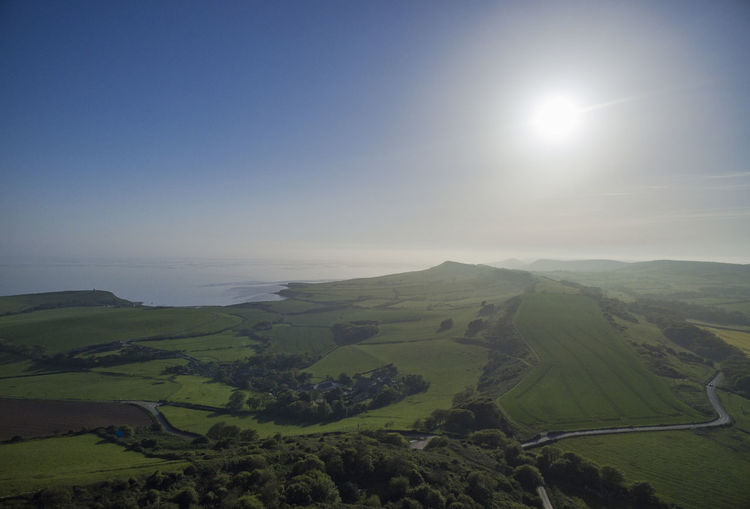 An aerial view of the village of Kimmeridge in Dorset on the Jurassic coastline. Sky Scenics - Nature Landscape Environment Beauty In Nature Tranquil Scene Tranquility Nature Sun No People Sunlight Land Non-urban Scene Day Idyllic Horizon Lens Flare Horizon Over Land Field Plant Outdoors Rolling Landscape Kimmeridge Bay
