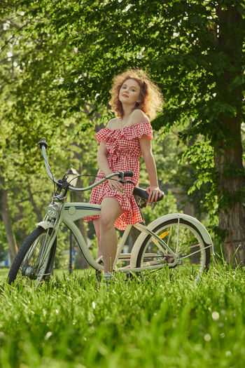 Full length of woman on bicycle in field