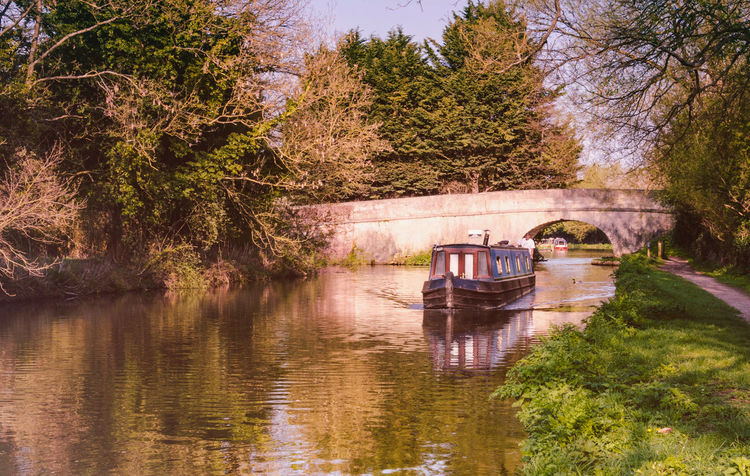 A canal boat motors down The River Kennet in Reading on a sunny April evening. Beauty In Nature Bridge Canal Boat Day Narrowboat Nature Outdoors Peaceful Quiet Reading River River Kennet Tranquil Tranquility Tree Trees Water Waterway