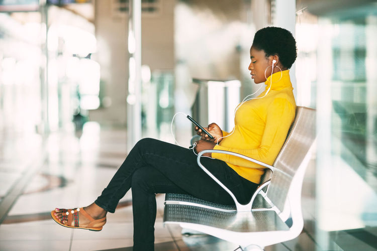 Beautiful african woman sitting on a chair in the waiting room, waiting for a subway train