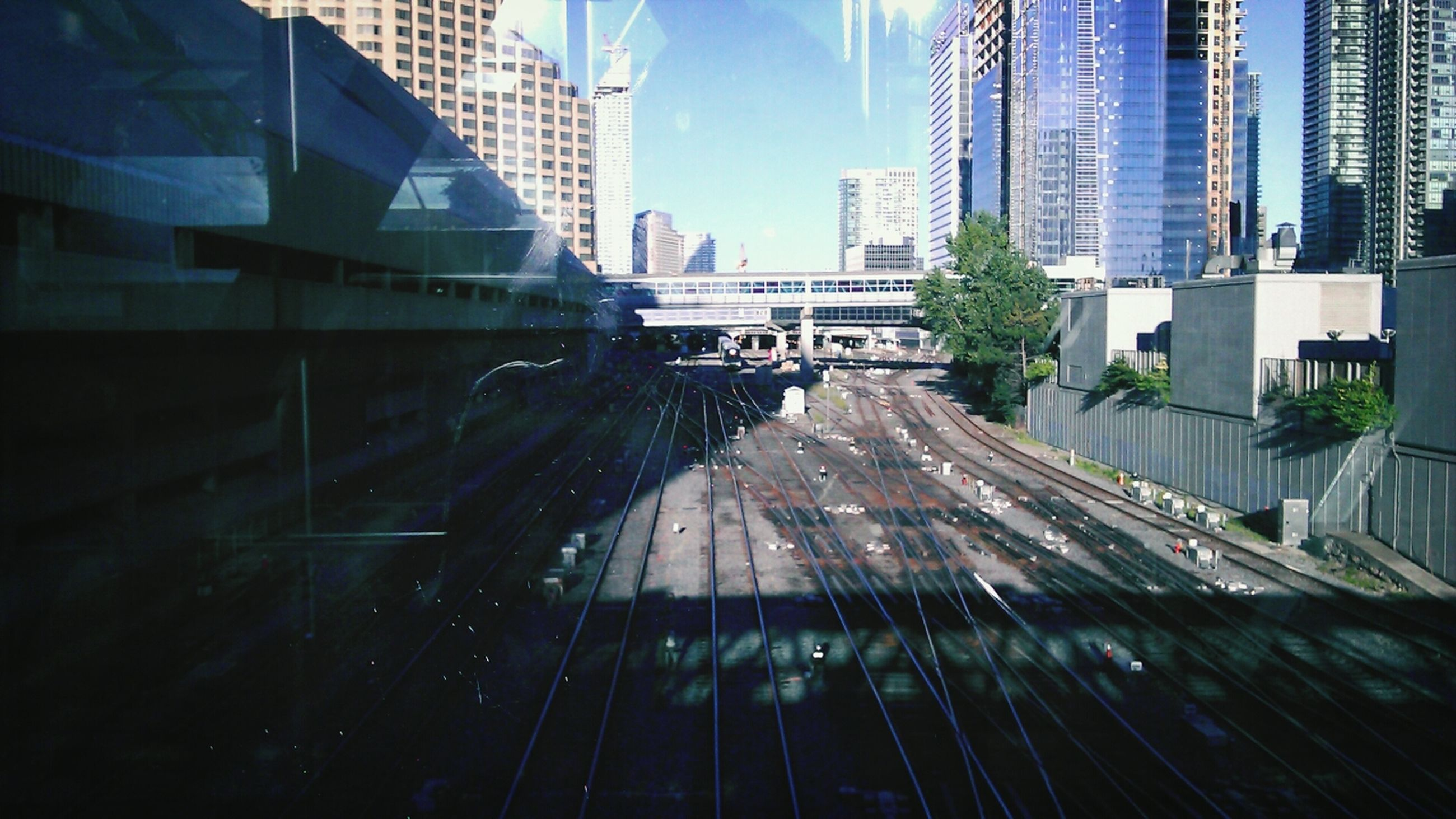 built structure, architecture, building exterior, transportation, railroad track, building, city, reflection, low angle view, men, day, outdoors, sky, glass - material, construction site, sunlight, modern