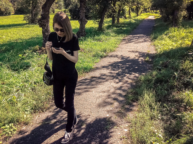 Carefree Casual Clothing Day Field Footpath Full Length Grass Green Color Innocence Leisure Activity Lifestyles Nature Outdoors Park - Man Made Space Person Shadow Sunlight Texting Tranquility Young Adult Young Women